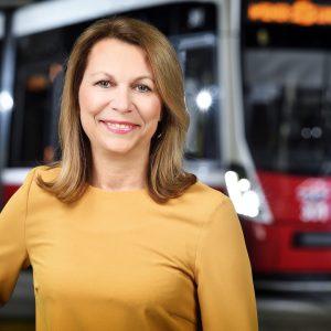 Alexandra Reinagl, Geschäftsführerin für Personal, Finanzen und Recht, vor einer Straßenbahn des Typs Flexity